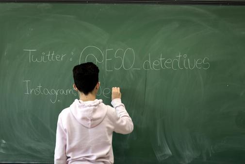 Un chico escribe en la pizarra de su clase