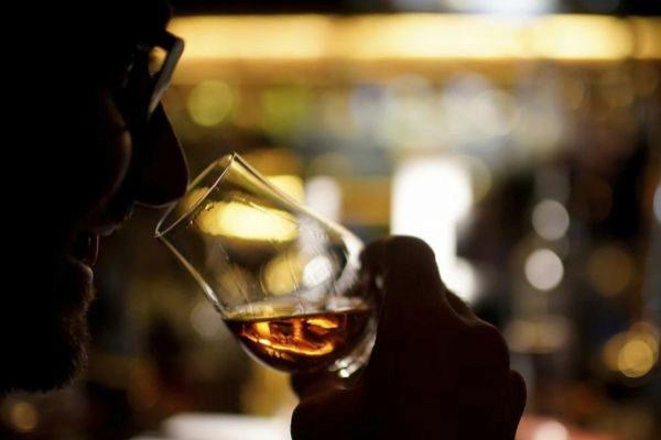 Un hombre bebe una copa de whisky en un bar de Shanghai.