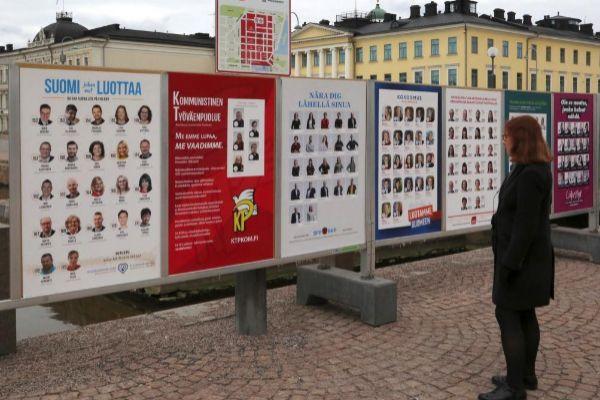 Votantes finlandeses observan los carteles electorales.