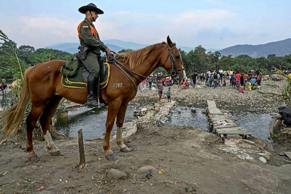 Un policía colombiano hace guardia en un paso clandestino.