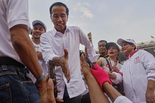 El presidente Joko Widodo choca las manos de sus seguidores en el estado de Jakarta.