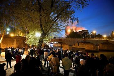 Decenas de personas en la orilla del río Sena observan la columna de humo y las llamas que consumen la catedral de Notre-Dame.
