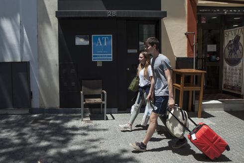 Unos turistas pasan frente a la fachada de un apartamento turístico en la calle Marques de Paradas en Sevilla.