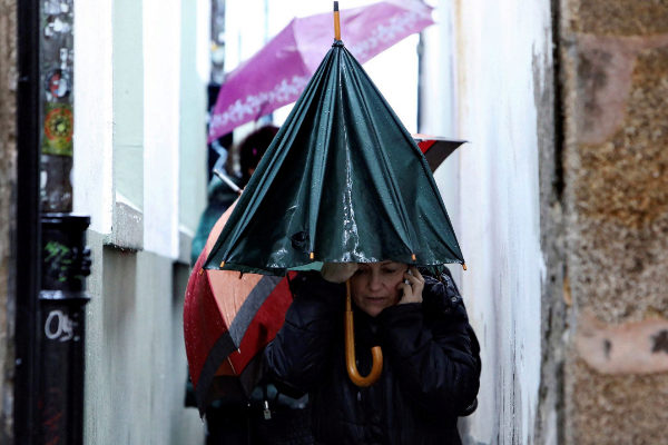 Peregrinos y turistas se protegen esta mañana de la lluvia en Galicia
