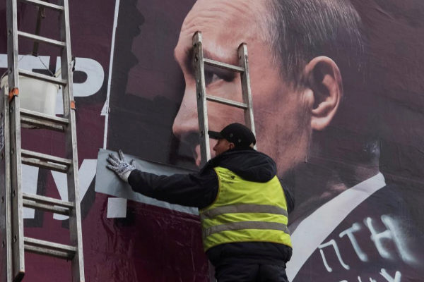 Un trabajador municipal retira un cartel electoral con la cara del presidente ruso Vladimir Putin.