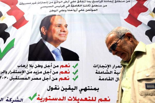 """Un hombre camina ante un pancarta que pide el """"Sí"""" a la reforma constitucional de Al Sisi."""
