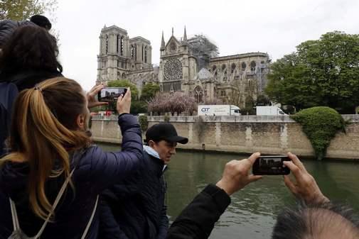 Varias personas fotografían con sus móviles la catedral tras el incendio.