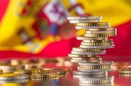Varias monedas y de fondo la bandera de España.