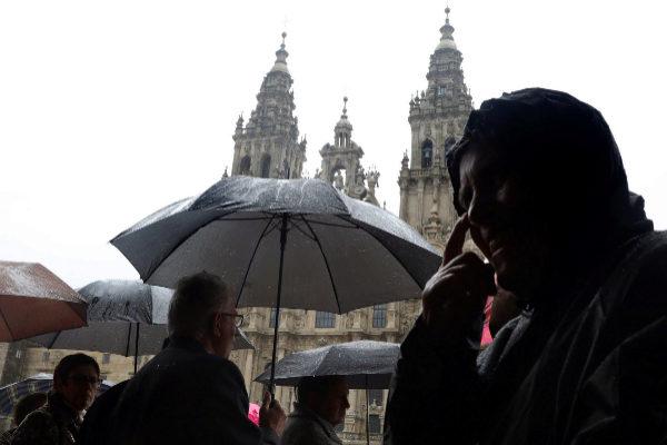 Varios peregrinos, bajo la lluvia, en Santiago de Compostela durante Semana Santa.