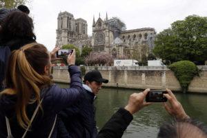Turistas y parisinos fotografían Notre Dame tras el incendio.