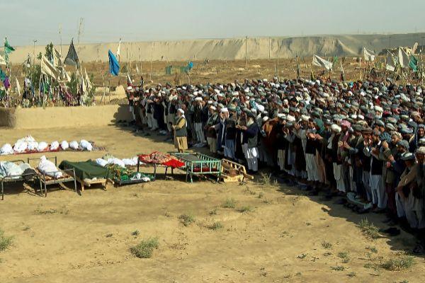 Ciudadanos afganos rezan en el funeral de varias víctimas por ataques aéreos, en Kunduz.