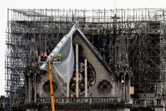 Workers intervene on the northern side of <HIT>Notre-Dame</HIT> Cathedral, on April 18, 2019 in Paris, in the aftermath of a fire that devastated the cathedral. - A huge fire swept through the <HIT>roof</HIT> of the famed <HIT>Notre-Dame</HIT> Cathedral in central Paris on April 15, 2019, sending flames and huge clouds of grey smoke billowing into the sky. The flames and smoke plumed from the spire and <HIT>roof</HIT> of the gothic cathedral, visited by millions of people a year. (Photo by ALAIN JOCARD / AFP)