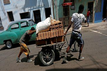 Dos hombres transportan ladrillos por una calle de La Habana.