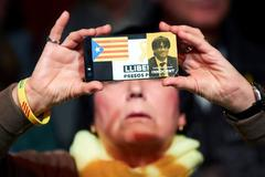 -FOTODELDIA- epa07500222 A woman takes a photo with her phone decorated with an image of former Catalan leader Carles Puigdemont and an '<HIT>Estelada</HIT>' flag during the election campaign opening event of the Catalan pro-Independence party JxCat in Barcelona, Catalonia, Spain, 11 April 2019. Spain will hold general elections on 28 April. EFE/Alejandro Garcia