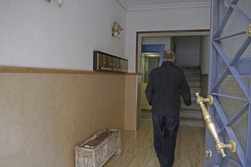 Un vecino entra en el portal del edificio de viviendas de Jaén donde se produjo la agresión sexual.