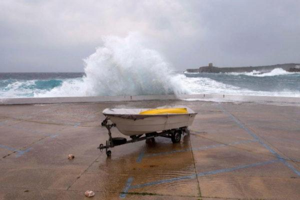 Una ola rompe en el paseo marítimo de Sant Lluís (Menorca).