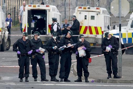 Policías de Derry recogen muestras en el lugar del asesinato.
