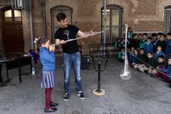 El maestro Diego Fernández enseña su arte a una niña.
