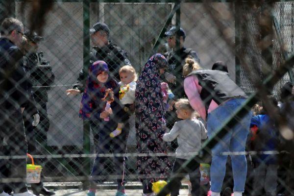 Policías custodian a mujeres y niños, familiares de yihadistas de Kosovo.