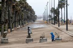 GRAFCVA4056. VALENCIA.- Las lluvias, el viento y los fenómenos costeros mantienen este sábado en alerta de nivel naranja, de nivel importante, a diferentes zonas de Comunidad Valenciana, Murcia y las islas Baleares. En la imagen, una mujer cruza el paseo marítimo de Valencia cubierto en parte por la arena que arrastra el fuerte viento.