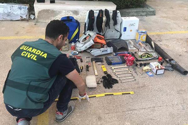 Un agente de la Guardia Civil junto a los objetos incautados durante la operación