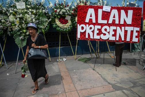 Una mujer pasa junto a coronas de flores en el velatorio de Alan García.