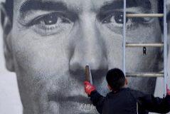 Un operario fija un cartel electoral de Pedro Sánchez.