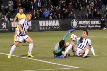 Dos jugadores del Castellón pugnan por el balón con el portero rival.