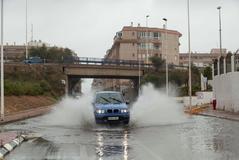 Un vehículo circula por una calle inundada en la zona del Parque de las Naciones de Torrevieja (Alicante). Las fuertes lluvias registradas en las últimas horas en Torrevieja han obligado al Ayuntamiento del municipio alicantino a desalojar un zona de acampada, suspender el transporte urbano y recomendar a la población que no salga de sus casas.
