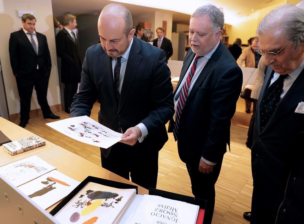 El presidente de la Comunidad de Madrid, Pedro Rollán, sujeta uno de los libros de la colección.