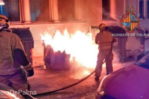 Dos bomberos sofocan el fuego de uno de los incendios provocados en los últimos meses en contenedores.