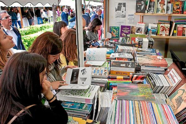 Unas jóvenes miran libros en una Feria del Libro.