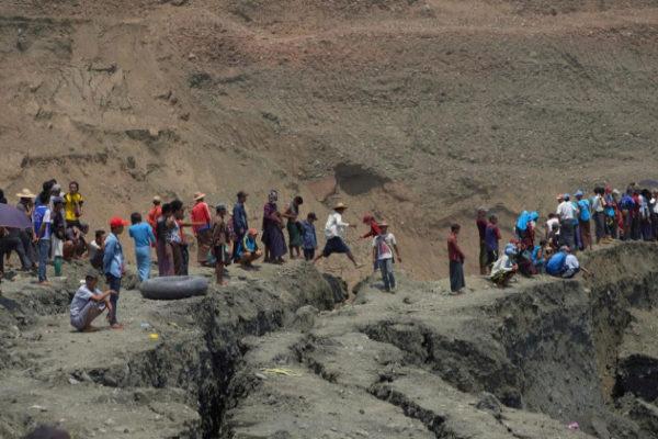 Un grupo de personas se asoman al lugar donde ha colapsado una mina arrastrando a los trabajadores en Hpakant.