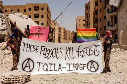 «Estos maricones matan fascistas», dice en inglés la pancarta de esta brigada en Raqqa. Detrás, la bandera arcoíris de la comunidad LGTB.