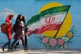 Un grupo de chicas jóvenes caminan delante de un mural con la bandera iraní en Teherán.