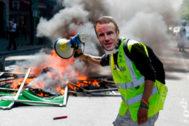 Un 'chalecos amarillo' porta una máscara satírica de Macron.