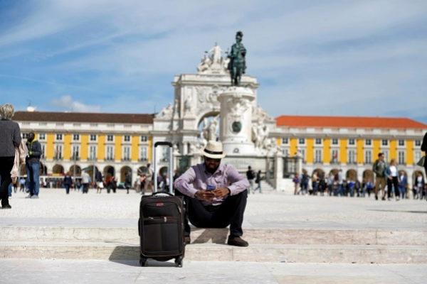 Un turista espera con su maleta en la Plaza del Comercio de Lisboa.
