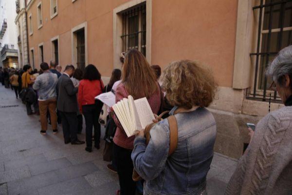 Decenas de personas hacen cola para asistir a un acto de la Noche de los Libros en la Real Casa de Correos.
