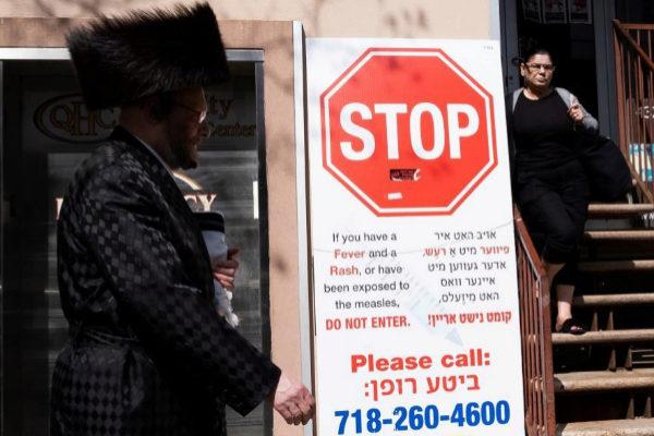 JLX01. BROOKLYN (ESTADOS UNIDOS).- Un hombre camina junto a un cartel...