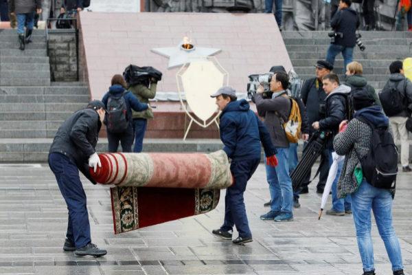 Trabajadores quitan la alfombra que estaba dispuesta para la ofrenda floral de Kim Jong Un.