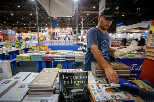 Un hombre coloca los precios de los libros en venta este jueves durante la 45 Feria Internacional del Libro de Buenos Aires (Argentina).