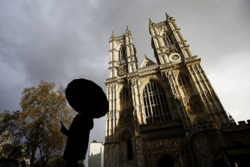 Una persona con paraguas camina frente a la Abadía de Westminster, en Londres.