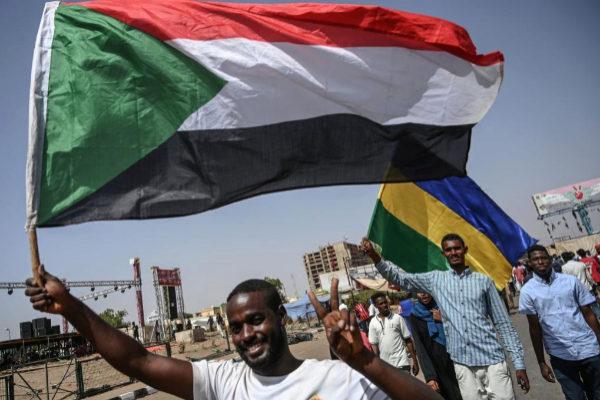 Protestantes sudaneses ondean la actual y la antigua bandera nacional sudanesa.