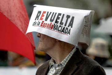 Un asistente se protege la cabeza con un cartel, durante la manifestación en marzo de las plataformas rurales bajo el lema 'Revuelta de la Espana Vaciada'.