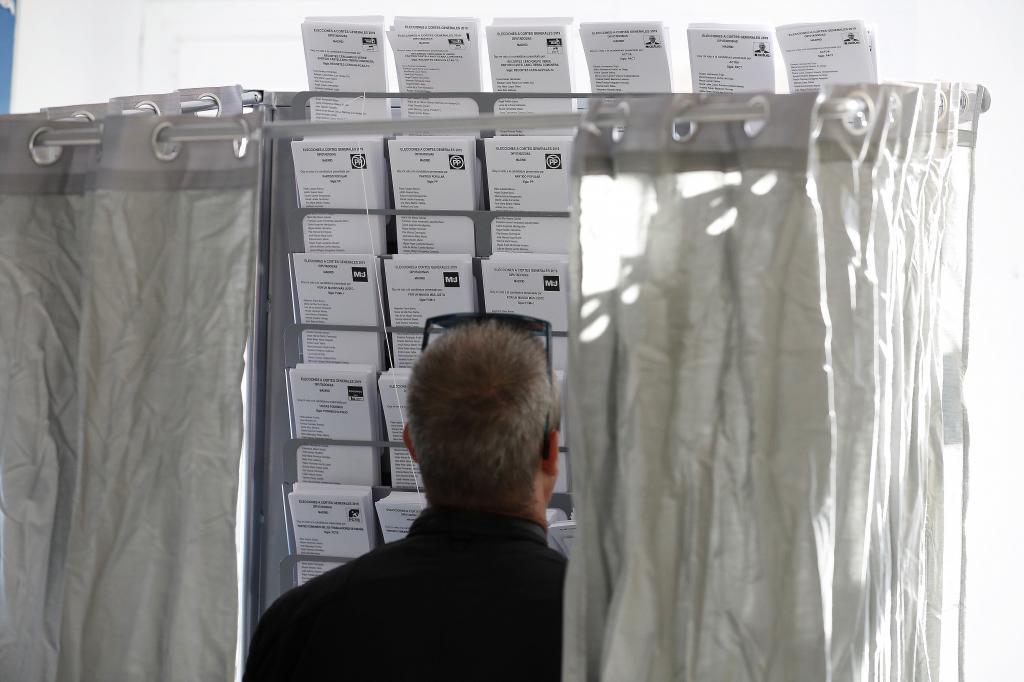 En la foto,una persona elige su papeleta electoral en el colegio Pinar...