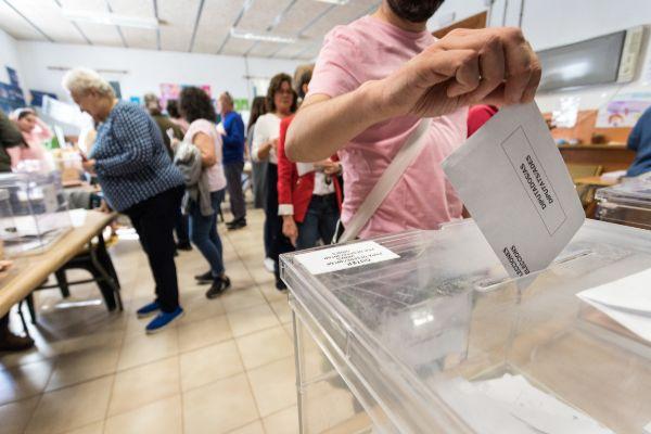 Un ciudadanos deposita su voto en un colegio electoral de Palma.