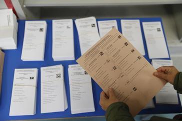 Un ciudadano coge una papeleta para el Senado en un colegio electoral.
