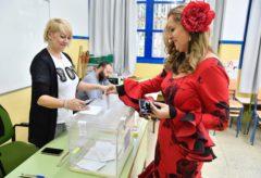 Una mujer vestida de flamenca vota en El Ejido (Almería), donde este domingo celebraban la fiesta de San Marcos.