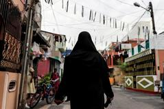 A <HIT>Muslim</HIT> woman wearing a hijab walks through a street near St Anthony's Shrine in Colombo