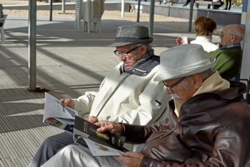 Dos jubilados leen unas revistas en un banco del paseo marítimo de Benidorm.